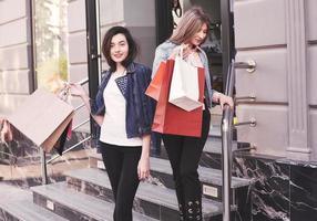 twee jonge vrouw die boodschappentassen draagt terwijl ze op de trap loopt na een bezoek aan de winkels foto