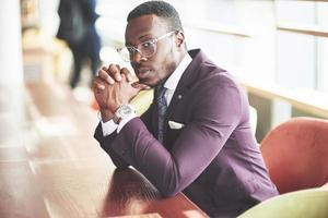 een mooie Afro-Amerikaanse zakenman leest in een café. foto