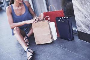 mooi jong meisje zit met boodschappentassen op straat en is blij met haar nieuwe kleren foto