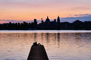 paar zittend op de pier kijkend naar de zonsondergang en de skyline van de stad foto