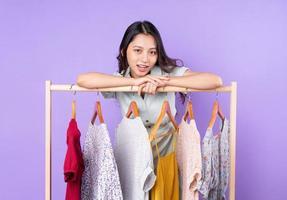 afbeelding van mode vrouw in rok staande in de buurt van kledingkast met kleding en kiezen wat te dragen geïsoleerd op paarse achtergrond foto