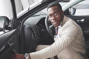 stijlvolle zwarte zakenman zit achter het stuur van nieuwe luxeauto. rijke afro-amerikaanse man foto