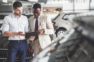 een jonge zwarte zakenvrouw ondertekent documenten en koopt een nieuwe auto. de autodealer staat naast hem foto