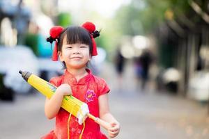 mooi Aziatisch meisje met paraplu met gesloten, gele vintage stijl. kinderen glimlachen lief en gelukkig. kind droeg een rode chinese nieuwjaarsjurk en een harige rode haarclip. schattig kind 3-4 jaar oud. foto