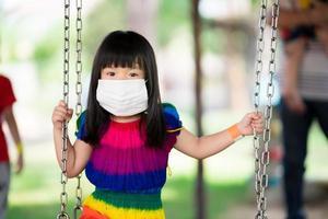 schattig meisje draagt een wit medisch gezichtsmasker om de verspreiding van coronavirus covid 19 te voorkomen, klein kind zat op de schommel in een druk park, een 4-jarig kind draagt een kleurrijke jurk, nieuw normaal foto