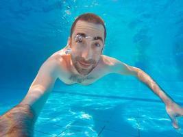 jonge knappe man die onder water duikt in een zwembad foto