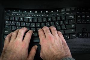 man typt op een toetsenbord met letters in het hebreeuws en engels foto