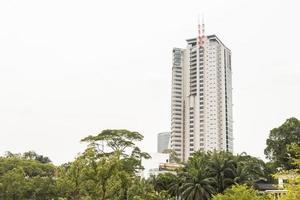 op de achtergrond een hoog gebouw wolkenkrabber perdana botanische tuinen. foto