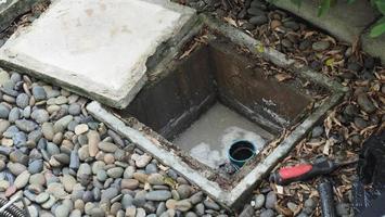 afvoer reiniging. loodgieter die verstopte vetvanger repareert met vijzel foto