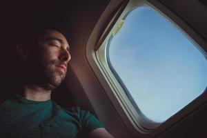 jonge man rusten en slapen in een vliegtuig foto
