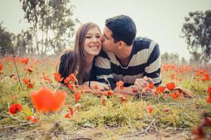 man kust vrouw en ze heeft een brede glimlach terwijl ze op het gras liggen in een veld met rode klaprozen foto