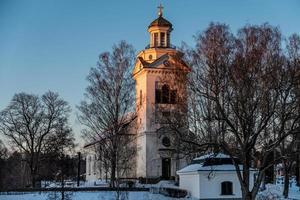 witte kerk in oranje en roze avondzon foto