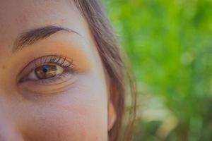 vrouw bruin oog close-up in het park foto