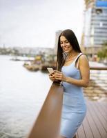 jonge vrouw met behulp van een mobiele telefoon terwijl ze aan de rivierpromenade staat foto