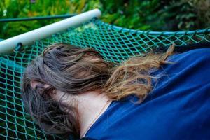 vrouw die in een hangmat ligt en haar gezicht bedekt met haar foto