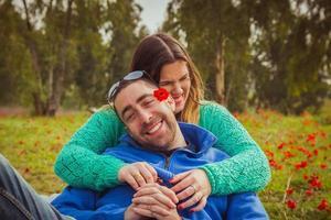 jong koppel zittend op het gras in een veld met rode papavers en glimlachen en lachen naar elkaar foto
