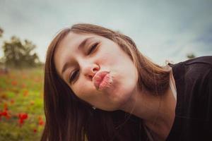 jonge vrouw die duckface-kus maakt terwijl ze een selfie-foto maakt met haar smartphone of camera op het gebied van rode klaprozen foto