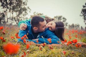 jong koppel liggend op het gras in een veld van rode papavers en glimlachen naar elkaar foto