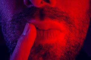 macro close-up op man met doordachte gezichtsuitdrukking met zijn vinger aan zijn lippen foto