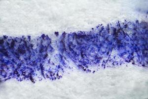 druipende blauwe inkt op papier onder de microscoop foto