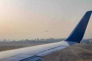 vliegtuigvleugel op de landingsbaan op de luchthaven ben gurion bij zonsopgang foto