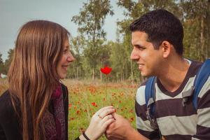 man die een vrouw een enkele rode anemoonbloem geeft in het veld met anemonen foto