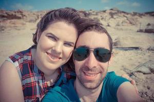 jong koppel selfie te nemen met smartphone of camera op het strand foto