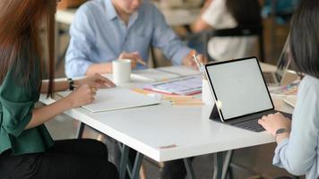 een team van professionele ontwerpers werkt met smartphone en laptops om applicaties te ontwerpen. foto