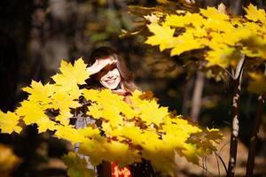jonge vrouw staat tussen gele herfstbladeren foto