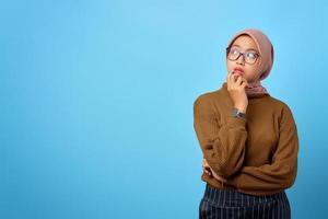 peinzende jonge aziatische vrouw kijkt serieus na over een vraag op een blauwe achtergrond foto