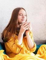 vrouw genietend van kopje koffie of thee zittend op een bank foto