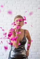 kaukasische vrouw die kleurrijke confetti de lucht in blaast foto
