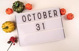 31 oktober lichtbak op witte tafel met pompoenen verspreid over foto