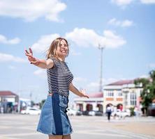 gelukkige jonge blanke vrouw die zich omdraait op de stedelijke achtergrond foto