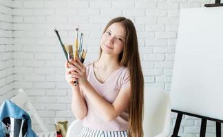 glimlachende vrouwenkunstenaar die penselen vasthoudt die in haar atelier werken foto