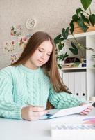 jonge lachende vrouw kunstenaar met kleurenpalet aan het werk in haar studio foto