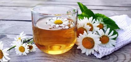 kamille aromatische thee close-up in een glazen beker op een houten achtergrond. zomerstilleven met wilde bloemen en geneeskrachtige kruidendrank. bloemen achtergrond. foto