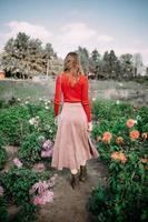 meisje in een rode jurk op een bloemenveld foto