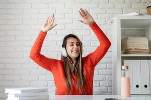 jonge blanke vrouw met oortelefoons dansend zittend aan tafel foto