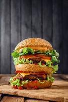zelfgemaakte dubbele hamburger op houten achtergrond foto