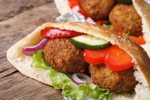 falafel in pitabroodjesclose-up op houten horizontale lijst foto