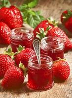 verse zelfgemaakte aardbeienjam met bessen in kleine potjes, selecteer foto