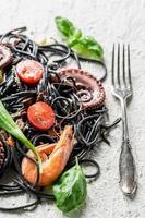 spaghetti met zeevruchten en zwarte pasta foto