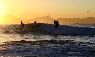 vier surfers op één golf foto