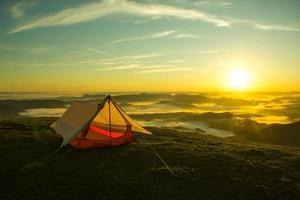 tent op de top van een berg met de zonsopgang foto