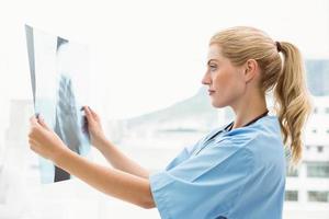 geconcentreerde vrouwelijke arts die röntgenstraal onderzoekt
