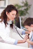 vrouwelijke arts onderzoekt de jongen met een stethoscoop foto