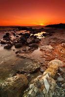 rotsachtige zeegezichtzonsondergang foto