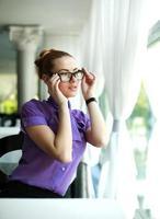 jonge zakenvrouw zitten aan de tafel in het restaurant foto