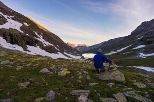 een persoon die zonsopgang hoog in de Alpen bekijkt